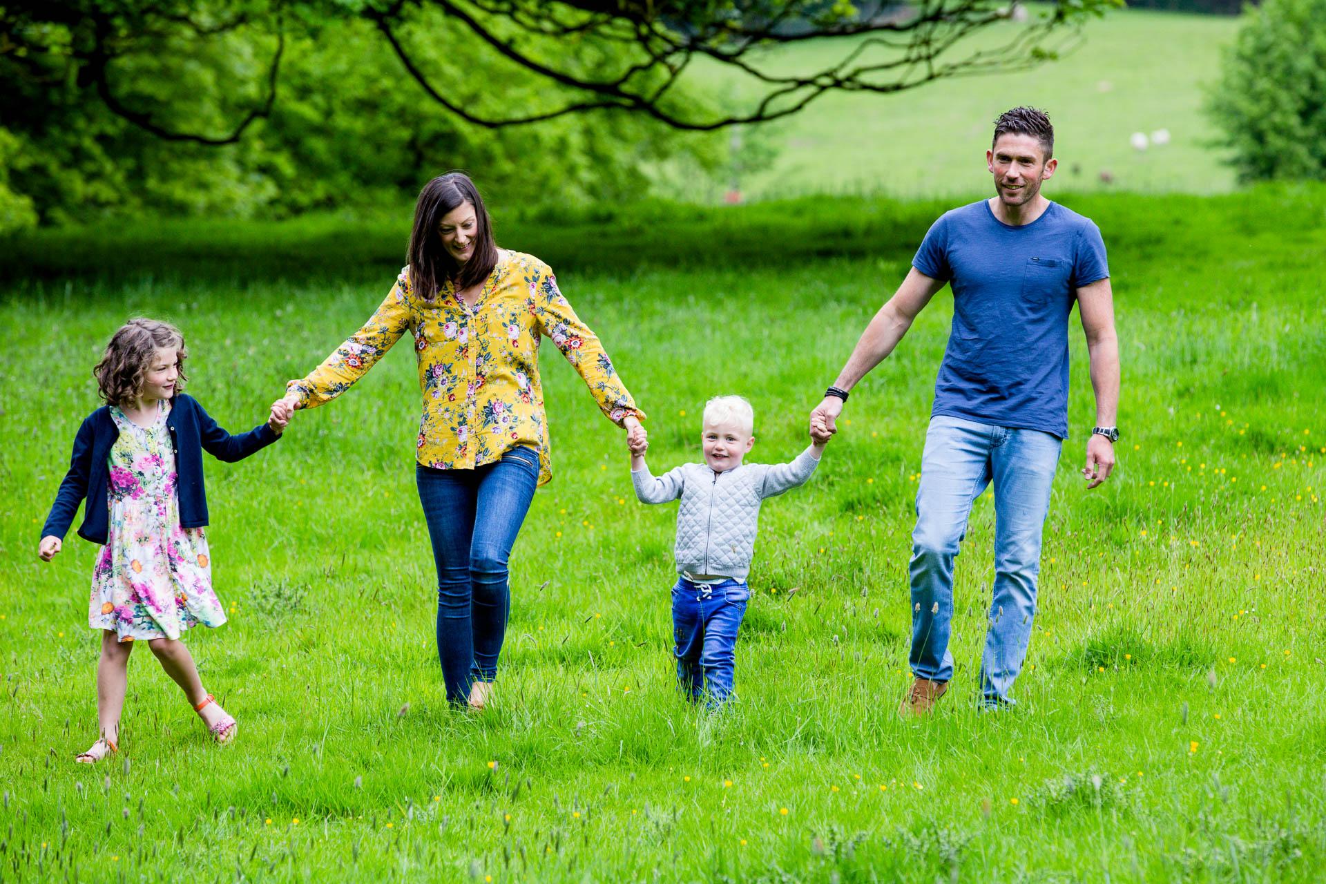 family walking hand in hand in field