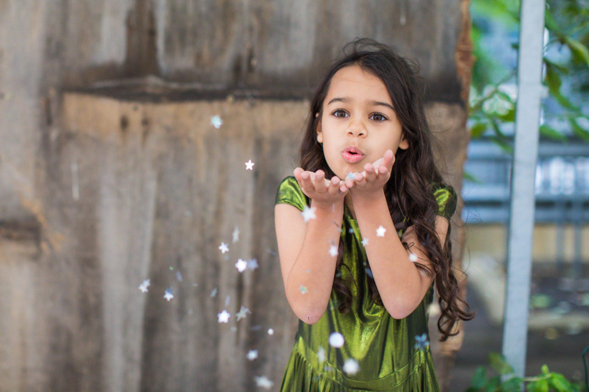 girl in green dress blowing star confetti