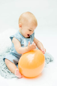 baby girl in blue dress playing with orange balloon