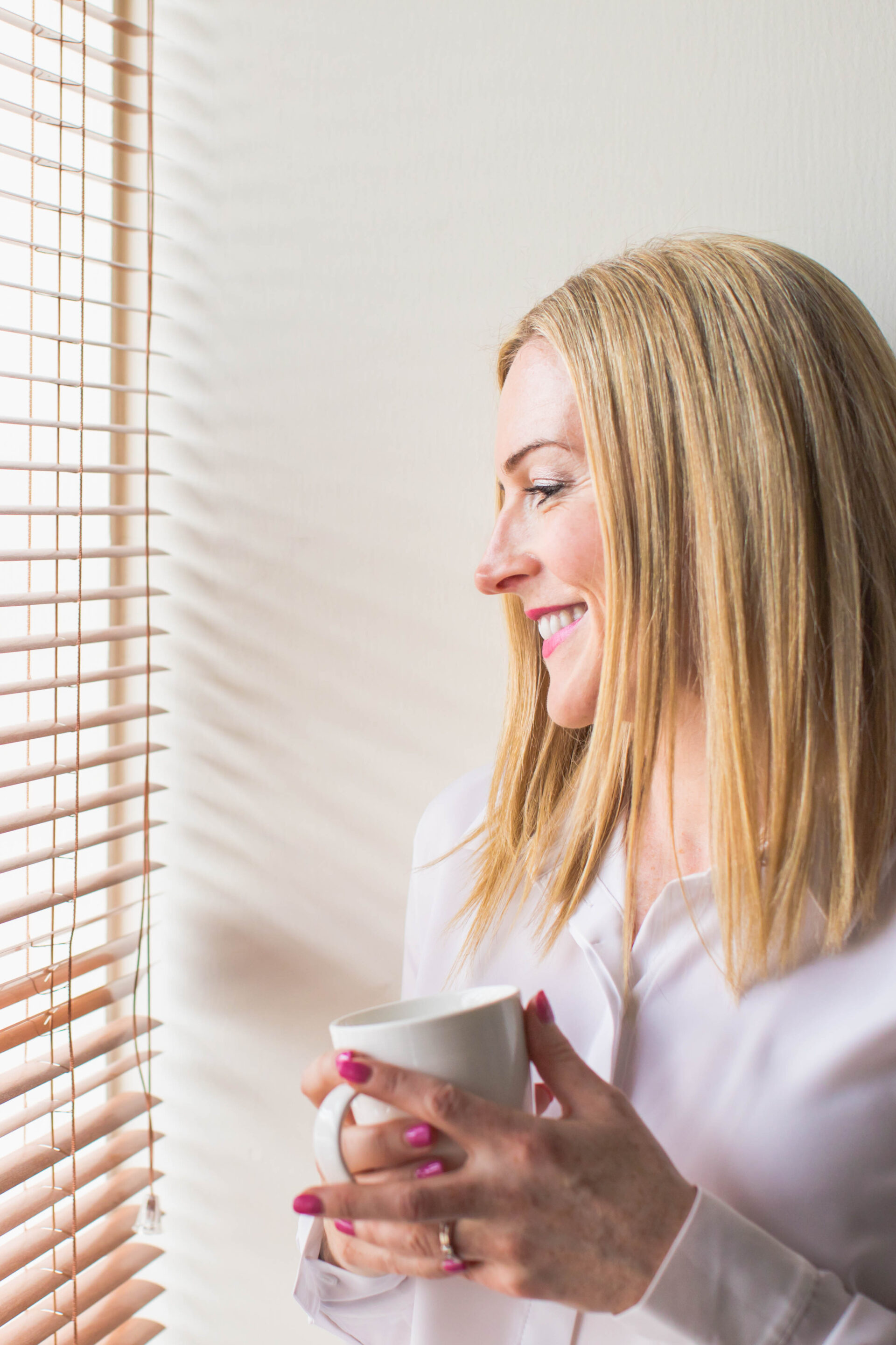 Female personal branding shot - woman with cup looking out window