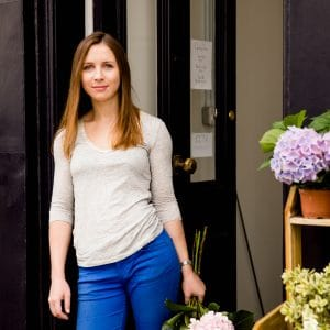 florist profile portrait in shop doorway with bouquet