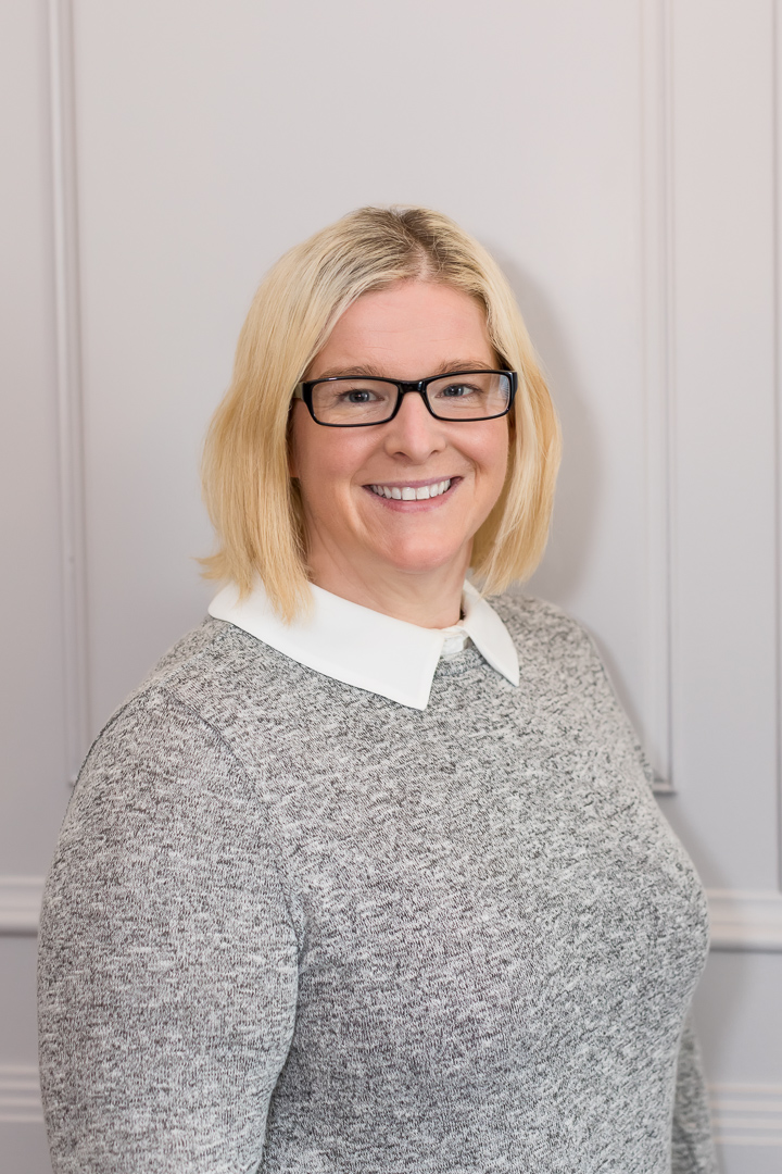 professional headshot of female small business owner in grey outfit with glasses