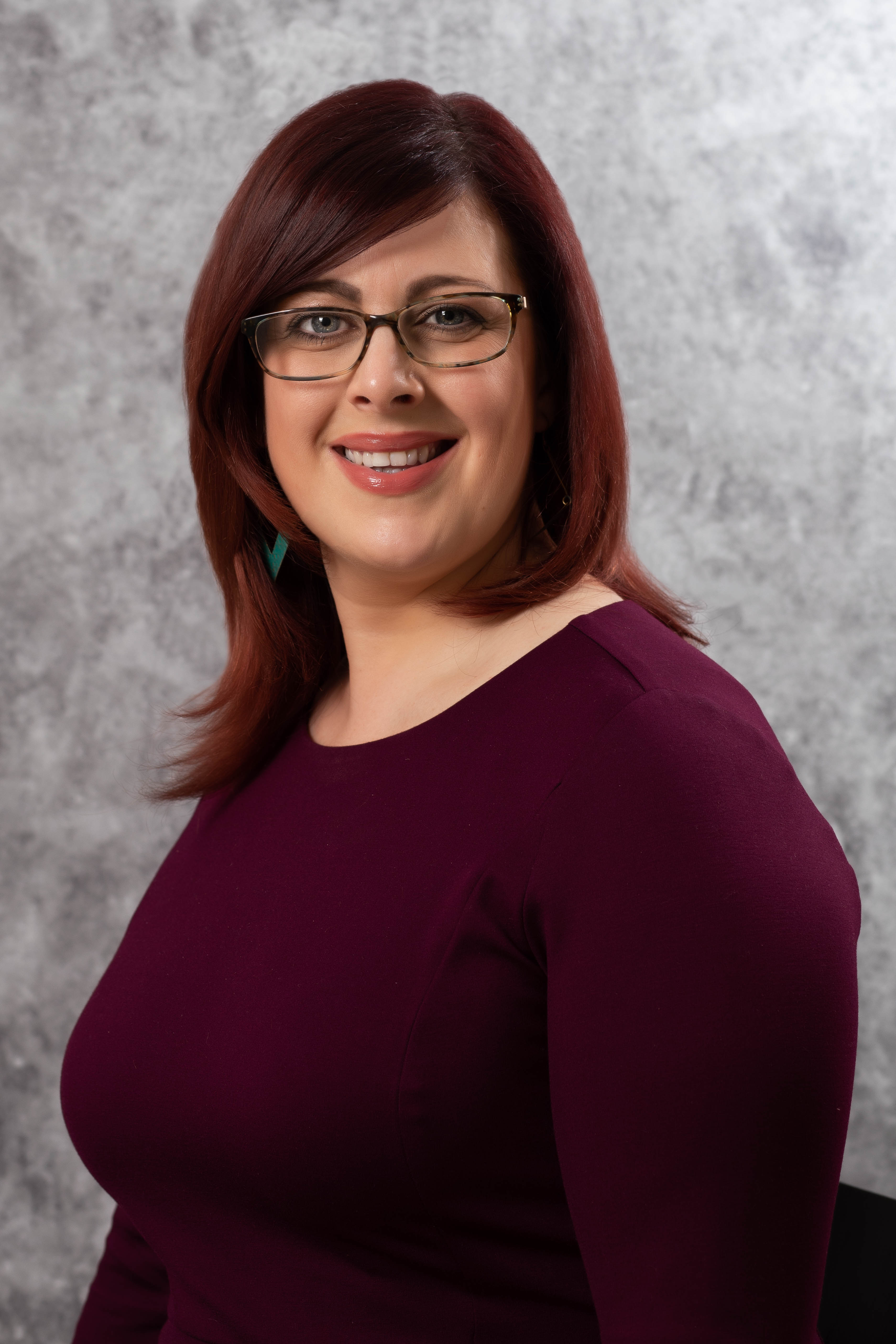 professional headshot of female businesswoman in plum dress and glasses