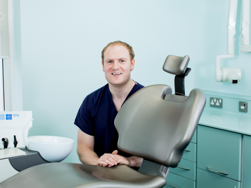 male dentist portrait with dental chair