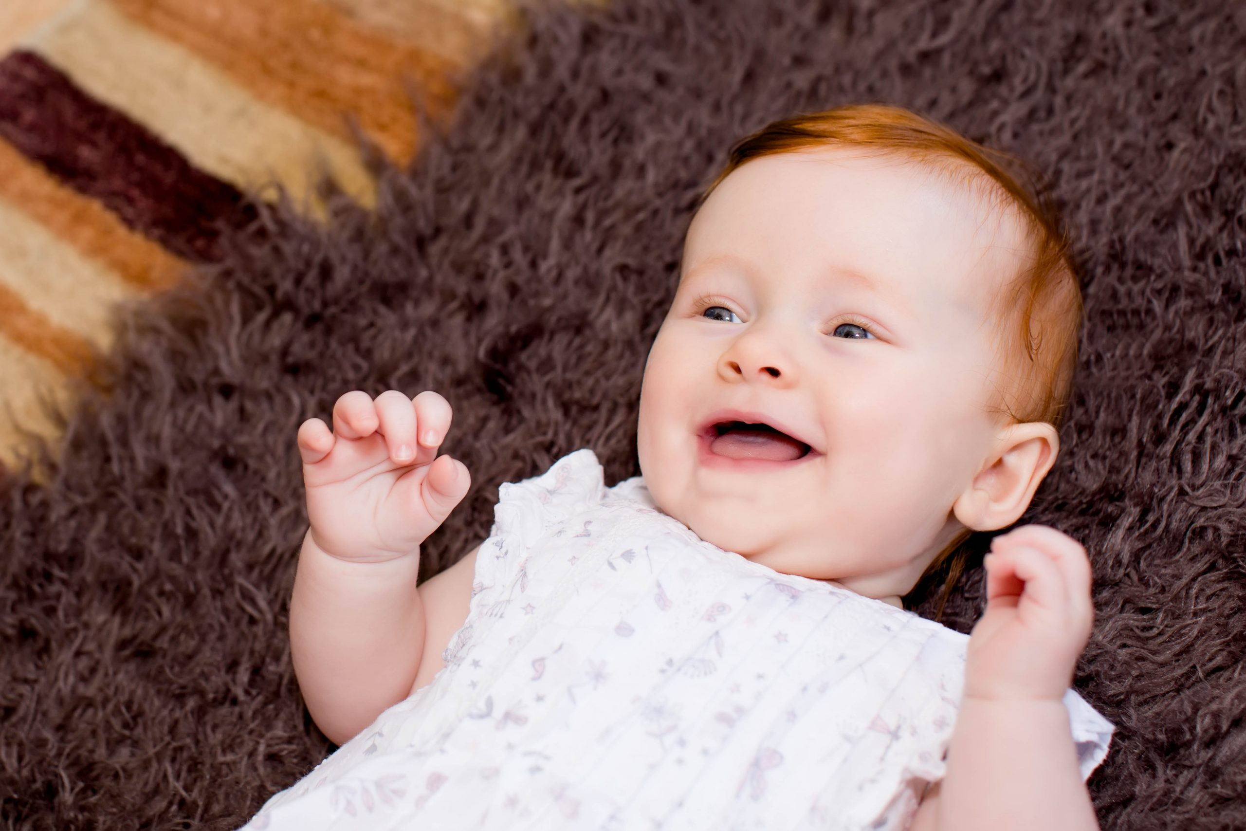 laughing baby on furry rug