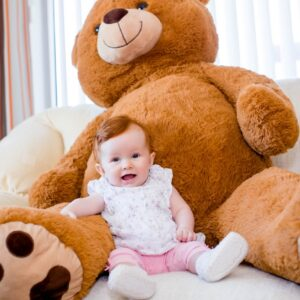 baby at home with giant teddy bear