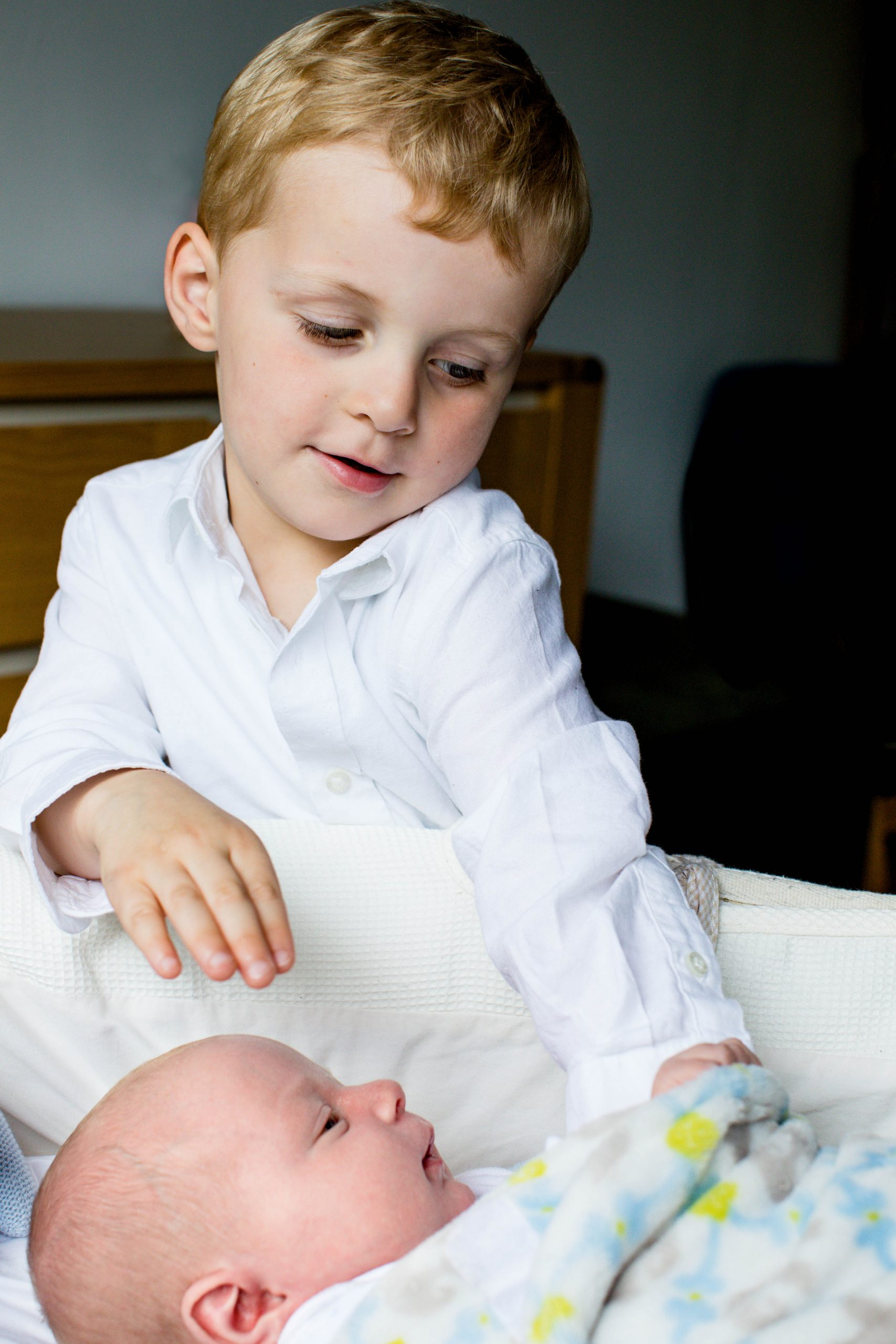 toddler sibling leaning into moses basket with baby brother