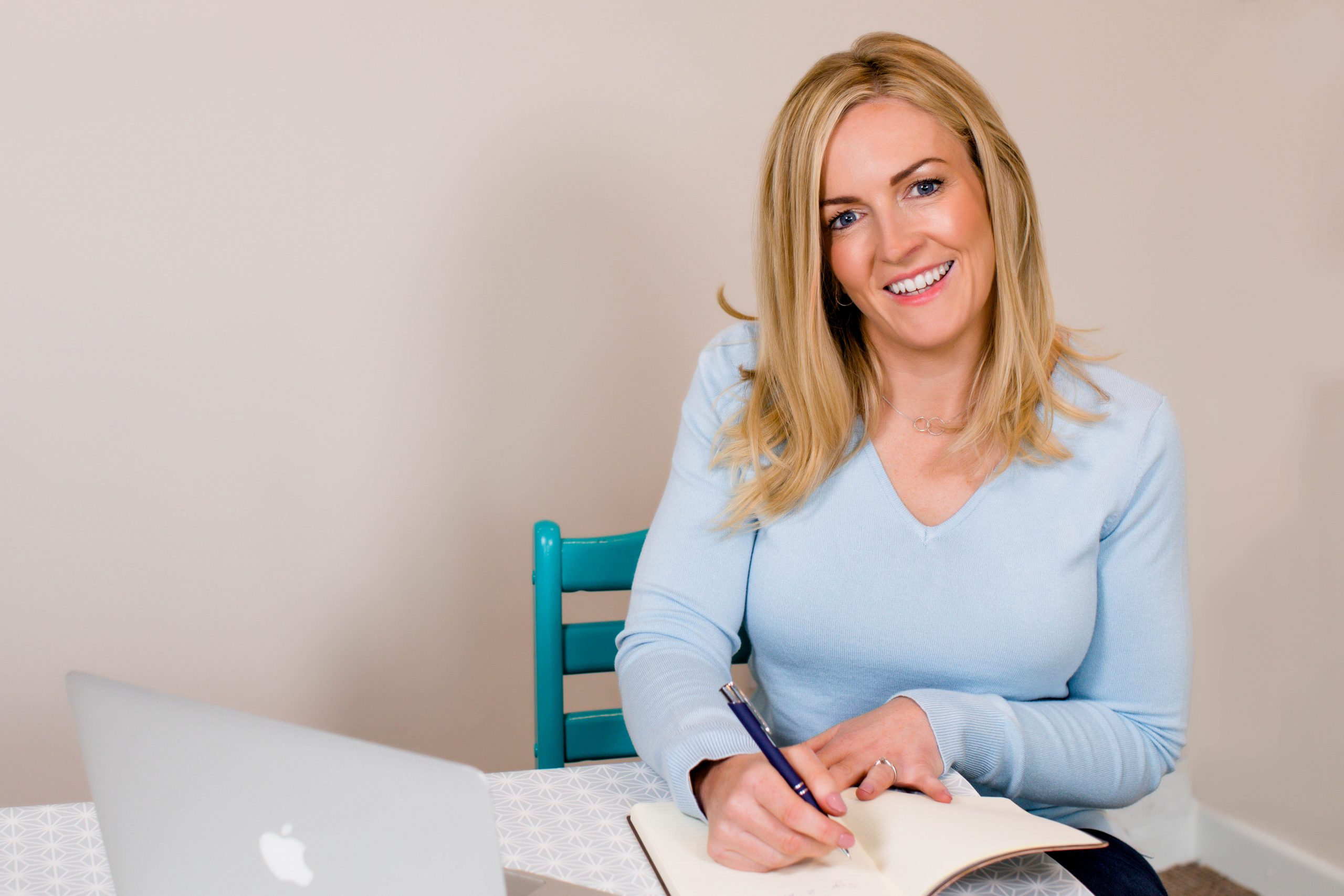 female entrepreneur writing in notebook