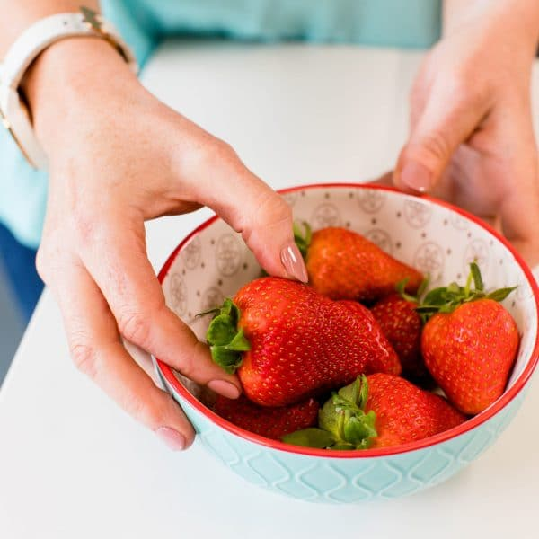 nutritionist hands with bowl of strawberries
