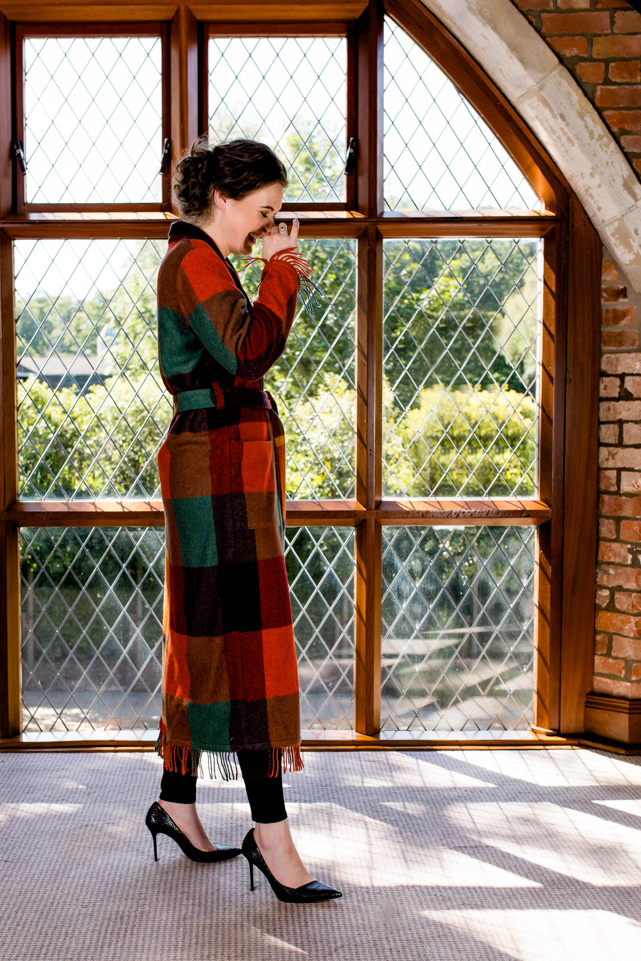 portrait of female textile designer laughing in arched window