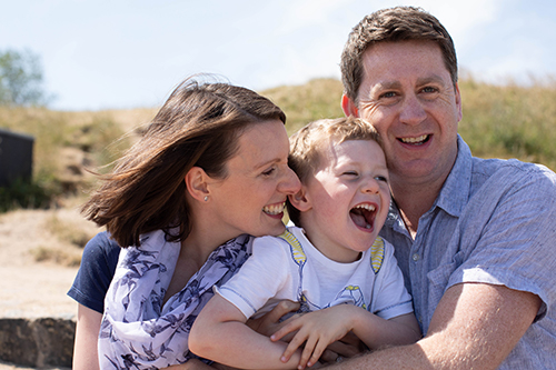 happy smiling laughing family of three outdoors
