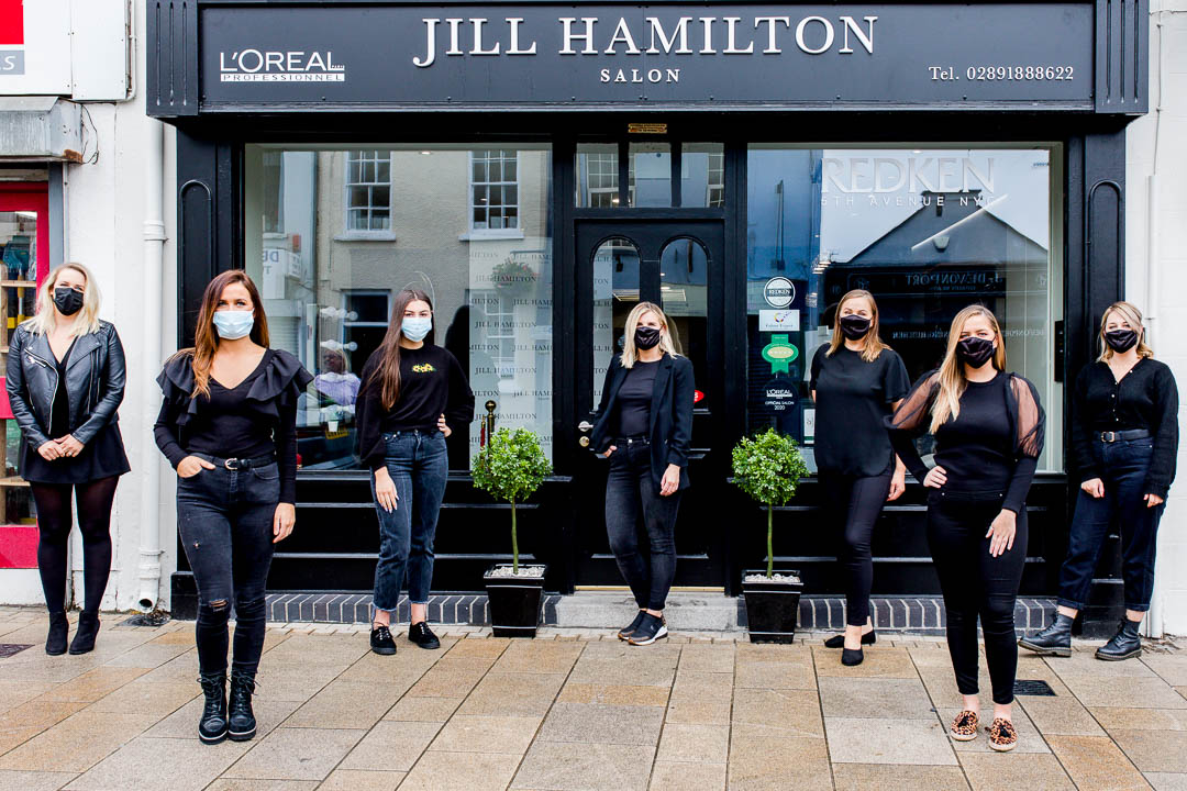business portrait of salon team of hairdressers at salon doorstep in masks