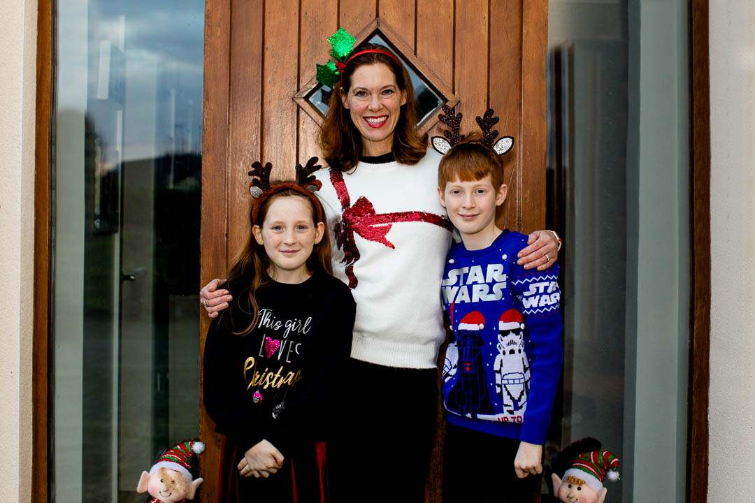 Family doorstep portrait - Mum with kids all in Christmas jumpers