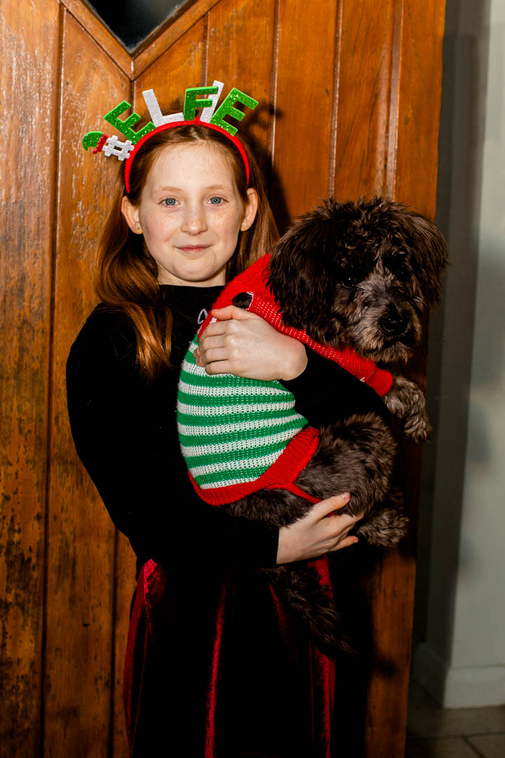 Christmas portrait of girl with dog in christmas outfits