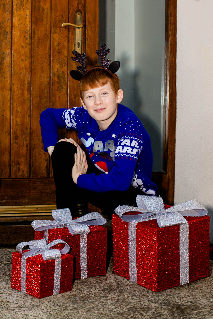 Portrait of boy in Christmas jumper with large present decorations