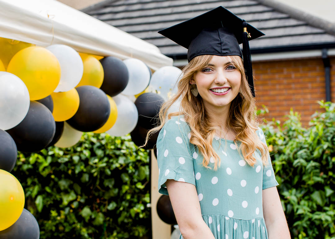 female graduate in cap with balloons background
